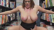 Bih titted brunette with sexy glasses riding hard cock in a library