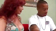 Redhead MILF with big boobs rides some black cock